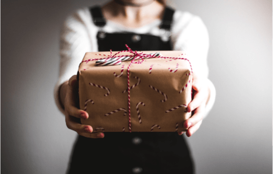 woman holding out a gift wrapped in brown paper and red ribbon