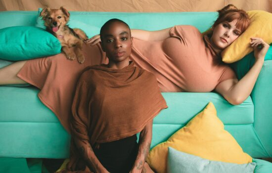 two people posing on a turquoise couch